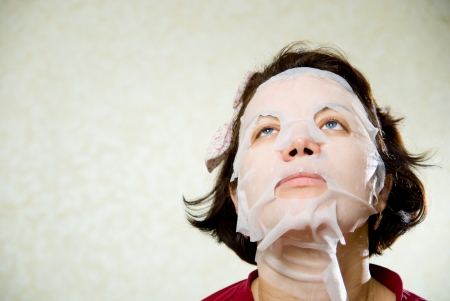 Closeup beauty portrait of woman with a mask on her face for treatment. photo