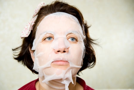 Portrait  woman applying rejuvenating facial mask on her face. photo
