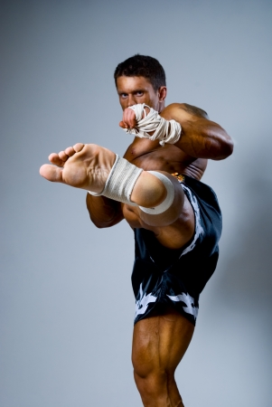 Kick-boxer kicks on a gray background. martial art