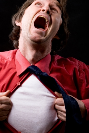 enraged: Enraged man rips off a red shirt on a black background Stock Photo