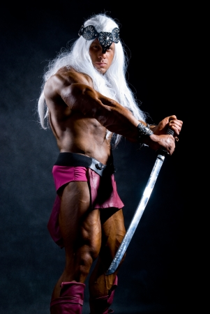 Naked muscular man warrior with a sword. Against a dark background Stock Photo - 17891979