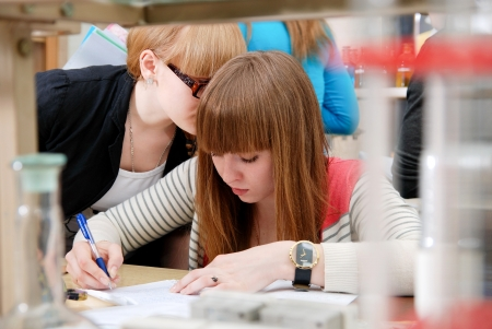 assistent: A student at work in the laboratory of chemistry makes notes in a notebook. She does hint girlfriend