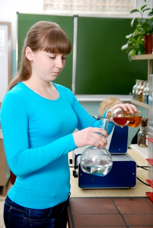 conducts: A student conducts an experiment in chemistry lab.
