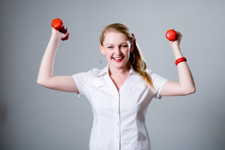 Merry successful businesswoman with raised dumbbells. On a gray background photo