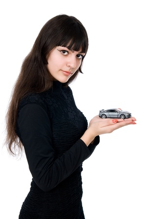 Portrait of young woman dreaming to purchase a new car against white background. photo