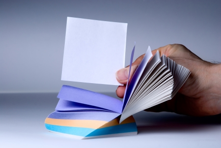 assert: Block of post-it notes. Hand shows a blank for notes Stock Photo