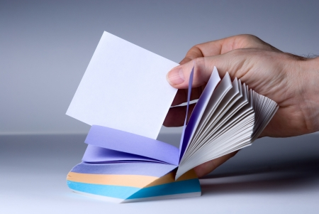 Block of post-it notes. Hand shows a blank for notes Stock Photo