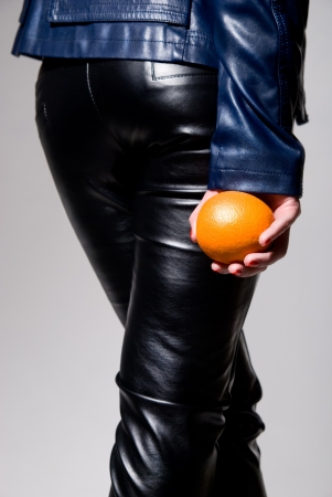 The girl in black leather pants with an orange in his hand. vertical photo photo