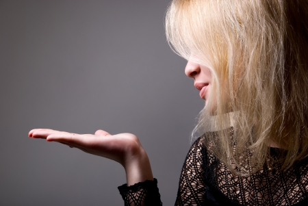 blow kiss: Portrait of a cute young female blowing a kiss towards copyspace - Grey background Stock Photo