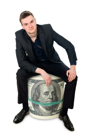 little business man: The young successful businessman sitting on a roll of money. Isolated on white background