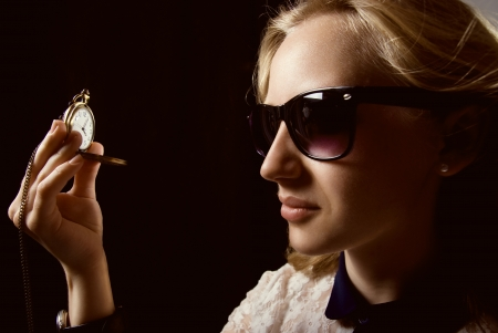 The girl in dark glasses holding a watch on a chain. On a black background in shades of yellow photo