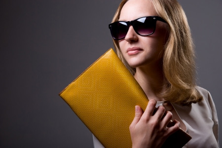 Portrait of a beautiful girl in sunglasses holding a clutch. On a gray background Stock Photo