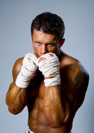 Experienced adult fighter punches during training. Kickboxing or muay thai photo