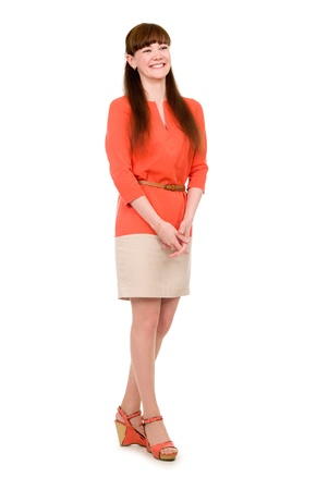Full-length portrait of a cheerful young girl in an orange dress. Isolated on white background