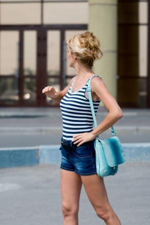 llegar tarde: Una mujer con un bolso de mano, mirando al pasado. Antes de que el edificio de cristal. Espero verlos Foto de archivo