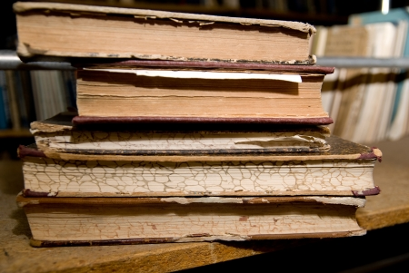 decrepitude: Old books lying on a shelf in the library.