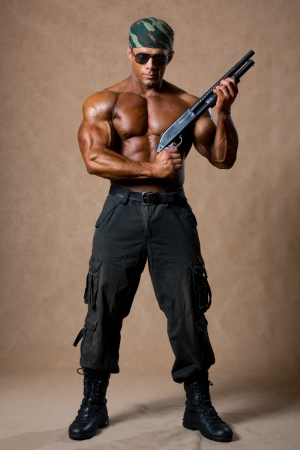 A muscular man with a gun in full view. The guy in the soldiers boots photo
