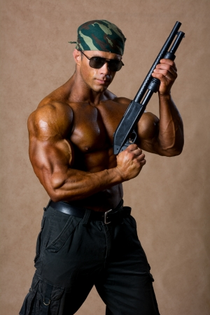 Portrait of a muscular man with a gun. photo