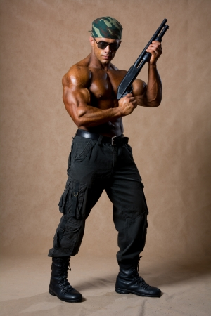 Portrait of a muscular man in a full-length with a gun. photo