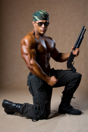 A muscular man with a gun. The guy in the soldiers' boots standing on one knee photo