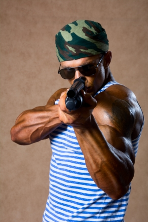 Strong athletic man with a gun. Special Forces soldier takes aim photo