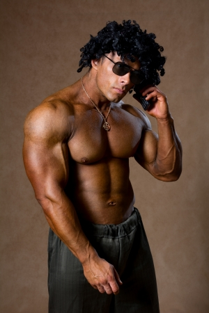 Muscular man with curly hair talking on a cell phone. Studio vertical photo of bodybuilder photo