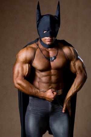 A muscular man in a Batman costume. Hero athlete with strong body photo
