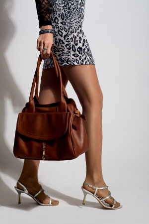 mini purse: Beautiful woman legs with a brown bag. Girl goes shopping, returning with shopping