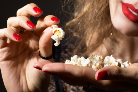 Close-up of young beautiful girl with popcorn in hand. Visiting the cinema photo