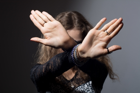 woman stop: Out of focus woman with her hands signaling to stop isolated on a black background Stock Photo