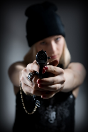 Portrait of a young girl with a gun. Hooligan in a dark cap targets the enemy. Sharpshooter Pistol photo