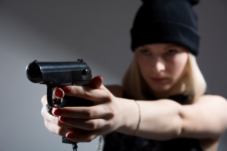 Portrait of a young girl with a gun in his hand. Hooligan in a dark cap targets the enemy. Sharpshooter Pistol photo