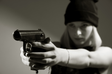 Portrait of a young girl with a gun in his hand. Hooligan in a dark cap targets the enemy. Sharpshooter gun. toned photo photo