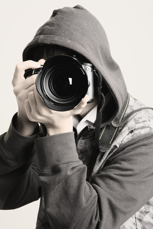 A young man in a hood using a professional camera.