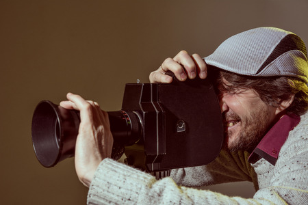 A man wearing a cap with an old movie camera. Shooting reportage, cinema Stock Photo - 25970210