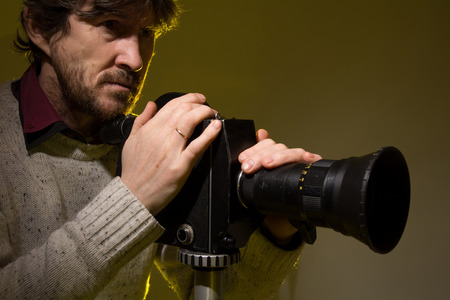 Man with old film movie camera. Shooting of the film, advertising and music video Standard-Bild