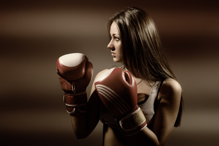 Young beautiful woman during fitness and boxing, a dark background photo