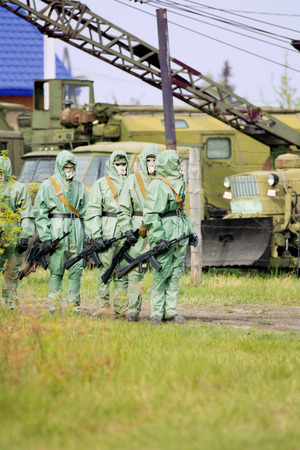 A group of soldiers with guns in their masks and protective clothing. On the background of military equipment photo