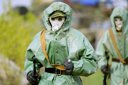 Military man in protective suit and gas mask outdoors. Are holding an automatic weapon photo