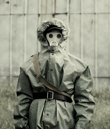 Military man in protective suit and gas mask outdoors. photo
