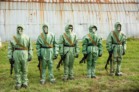 A group of soldiers with guns in their masks and protective clothing. photo