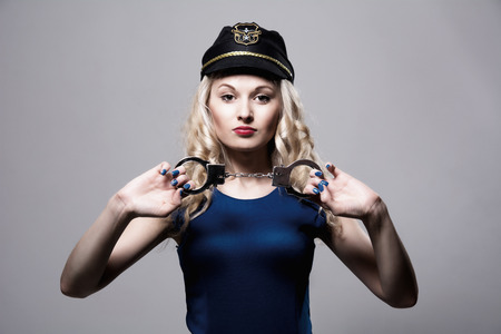 young  cuffs: Beautiful girl with handcuffs and a police cap. Isolated on gray background