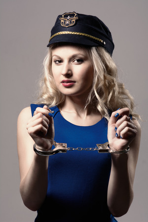 Beautiful girl with handcuffs and a police cap. Isolated on gray background