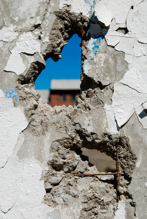Concrete wall with holes in several places. Crumbling wall of hostilities