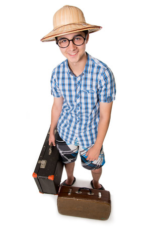 A young, attractive gay guy with glasses and two suitcases ready to travel. The stereotype of a foolish novice traveler. Portrait of a traveler in a full-length isolated on white background photo