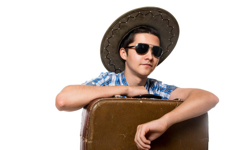 Close-up portrait of a young tourist. Traveler sunglasses and a hat with a suitcase. Isolated on white background photo