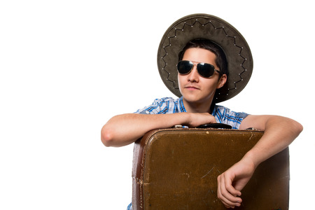 Portrait of a young tourist. Traveler sunglasses and a hat with a suitcase. Isolated on white background photo