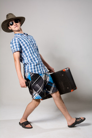 Portrait of a cheerful young guy tourist. A man with a suitcase going dark glasses and a hat photo