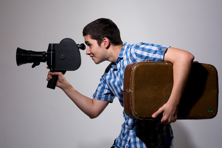 filmmaker: Young gay filmmaker with old movie camera and a suitcase in his hand. Stock Photo