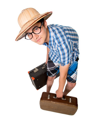 A young attractive man with glasses and two suitcases ready to travel. The stereotype of a foolish novice traveler. Portrait of a traveler in a full-length isolated on white background photo